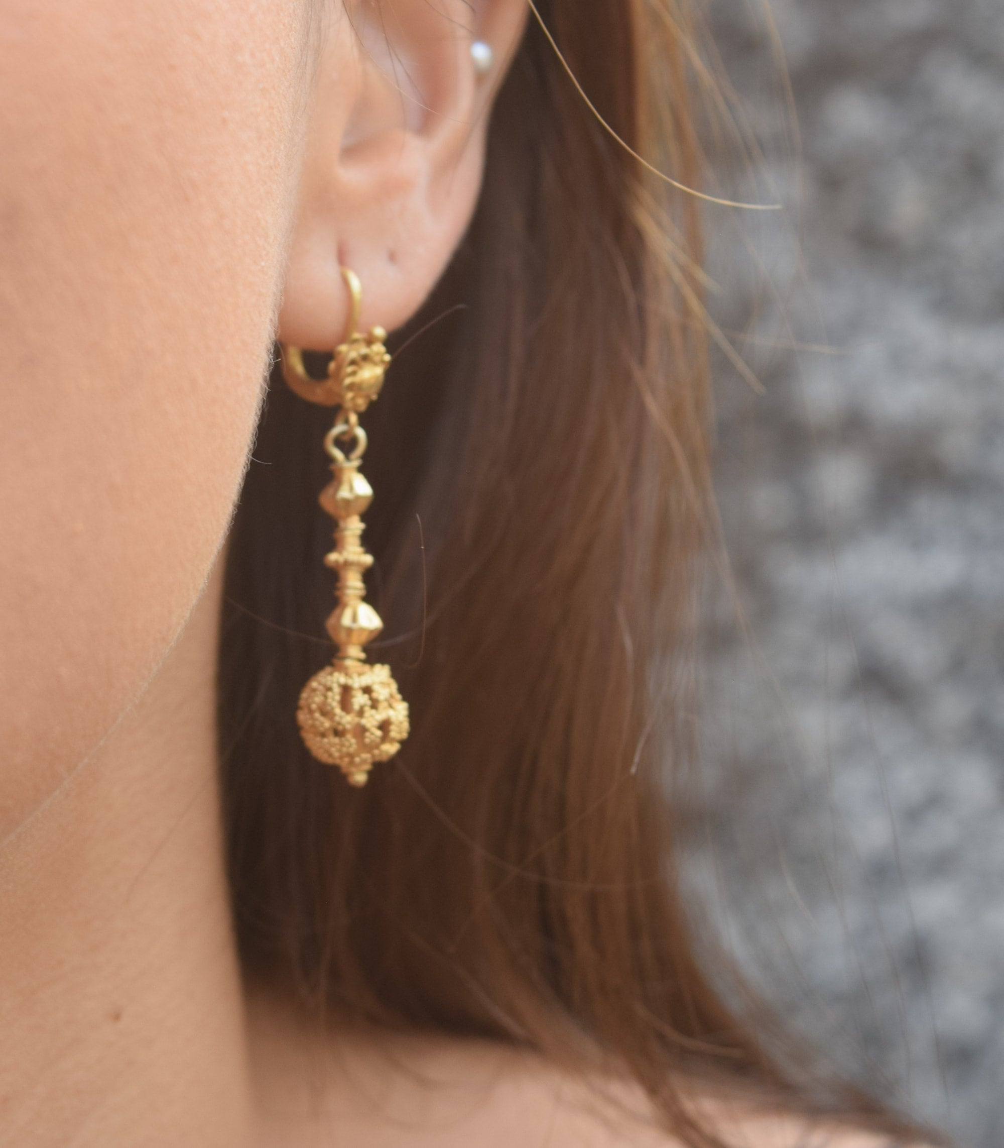 Amami Tambourine Dangle Earrings on a model close-up