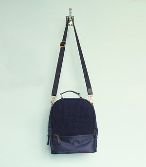 Cole Mini Backpack in Black hanging on a wall - Rags2Riches