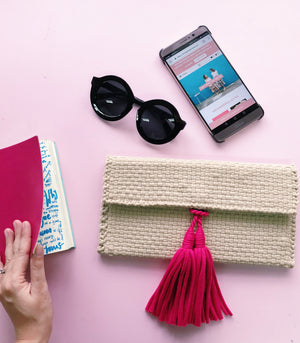 estelle mini clutch beige with fuchsia tassel with sunglasses and phone