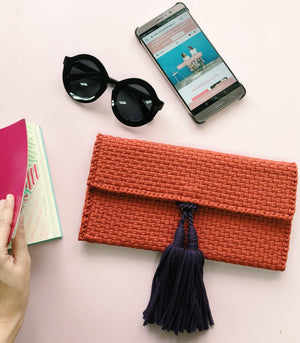 estelle mini clutch burnt orange with eggplant tassel with sunglasses and phone