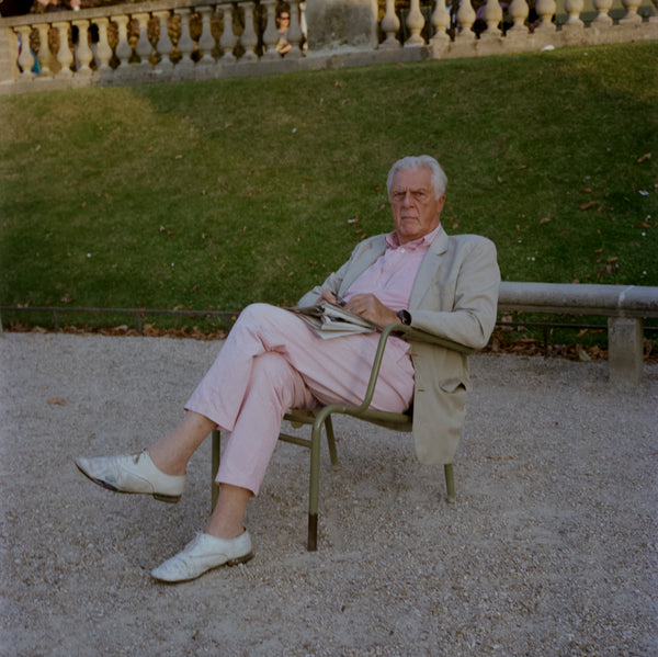 Man in grey jacket and pink pants sitting in a chair, photograph by film photographer Kir Lykkeberg