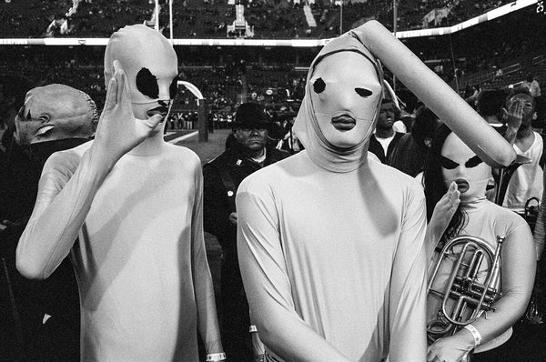 black and white photo of two people in masks at sporting event by Daniel Alvarez