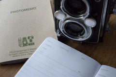 Two PhotoMemo film photography notebooks with a TLR film camera