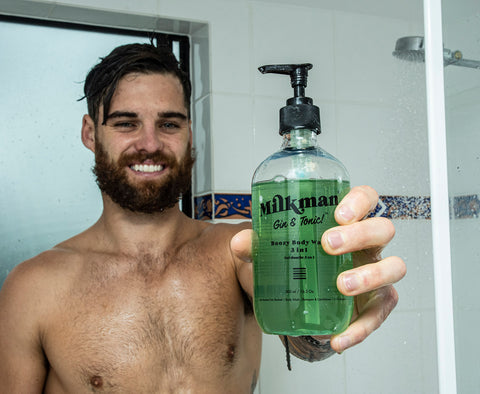 bearded man holding gin and tonic body wash shampoo & conditioner