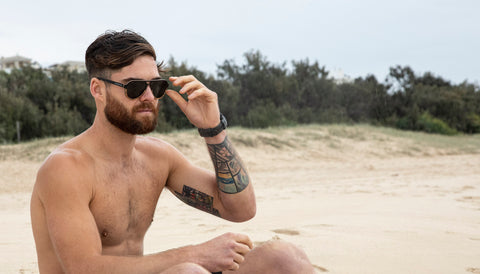 bearded man at the beach with wooden sunglasses from oakwood sunglasses company in sunshine coast queensland