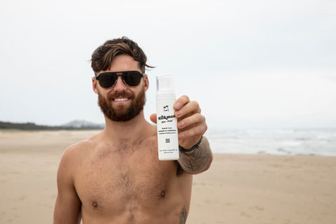 man holding 2 in 1 beard shampoo and conditioner