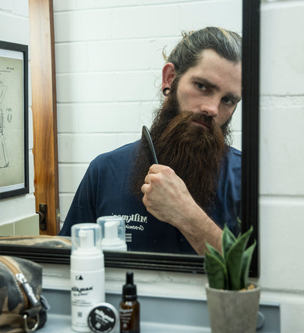 bearded man grooming beard with travel products