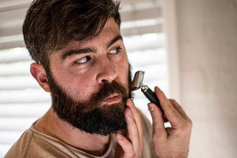 bearded man doing a cheek line up with double edge razor