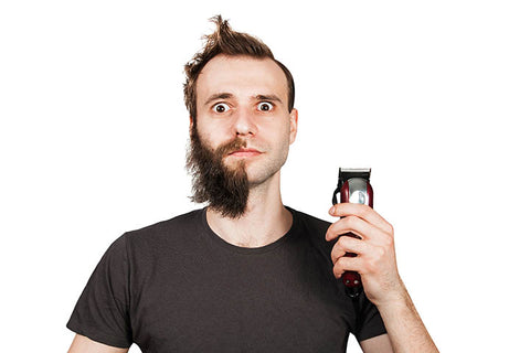 man using clipper to remove half of his beard