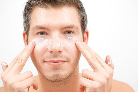 man rubbing moisturiser on face