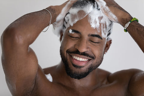 man with beard washing hair with a thick lather of shampoo