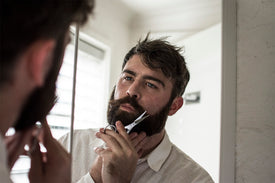 bearded man using beard scissors
