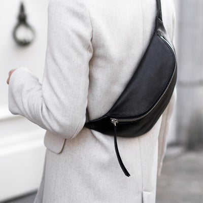 Oversized women's waist bag in black leather with bold zipper worn on back DAPHNY RAES