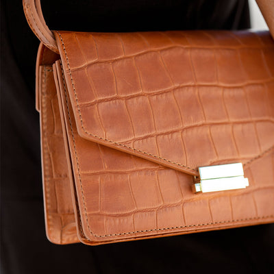 Detail of gold lock and cognac croco leather mini bag