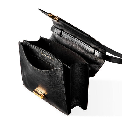 Inside compartments of black leather mini bag with stitched flap and gold lock