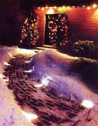 Cobble Lights on either side of a snowy paver lit sidewalk leading to a front door with Christmas Lit trees on both sides of door