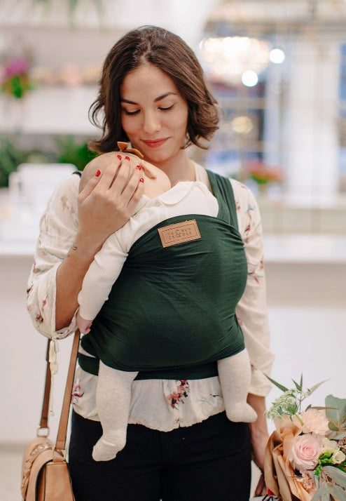 A woman with short medium brown hair holding a small bouquet of flowers and wearing a white top and black pants, carrying a baby with a deep green colored baby wrap carrier.