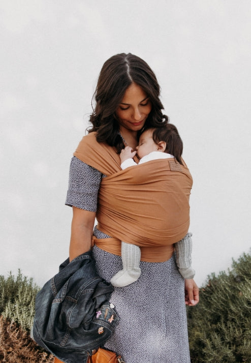 A woman with long dark brown hair holding a jean jacket and wearing a blue and white dress, carrying a baby with a sandstone colored baby wrap carrier.