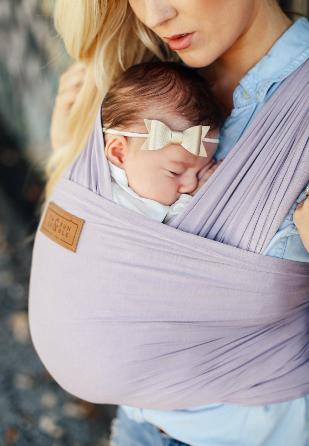 A woman with long blonde hair carrying a baby with a lavender colored baby wrap carrier.