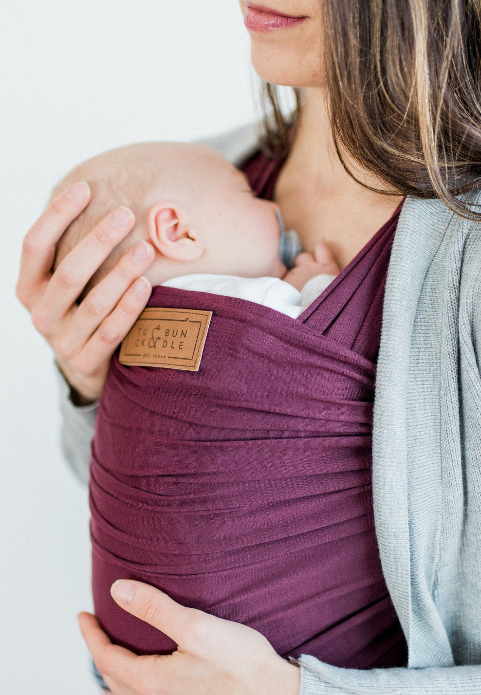 A woman with long medium brown hair carrying a baby with a deep purple-red colored baby wrap carrier.