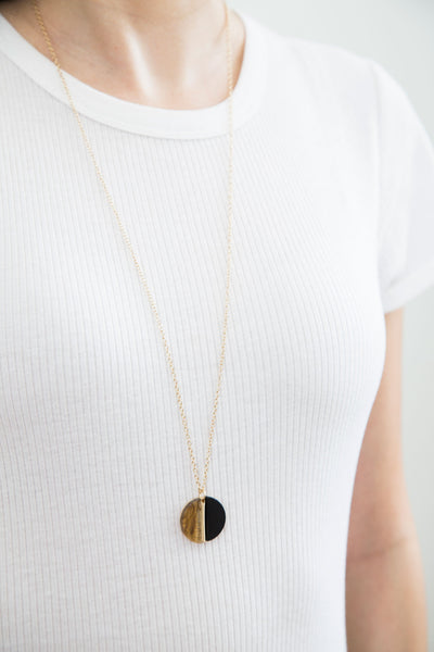 Hayden Necklace, modern elevated jewelry. Like a partially eclipsed moon, the light colored amber and black strike a perfect balance. On the flip side, a star radiating its light rays reaching all corners. The Hayden necklace can be worn both ways for an elevated look.