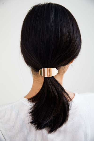 Naya Gold Hair Tie, modern hair accessories. The over-arching gold piece that looks pretty in your hair. Pull your hair back with this charming hair tie that we can't resist. Adds an effortlessly classy look that shines in any hairstyle.