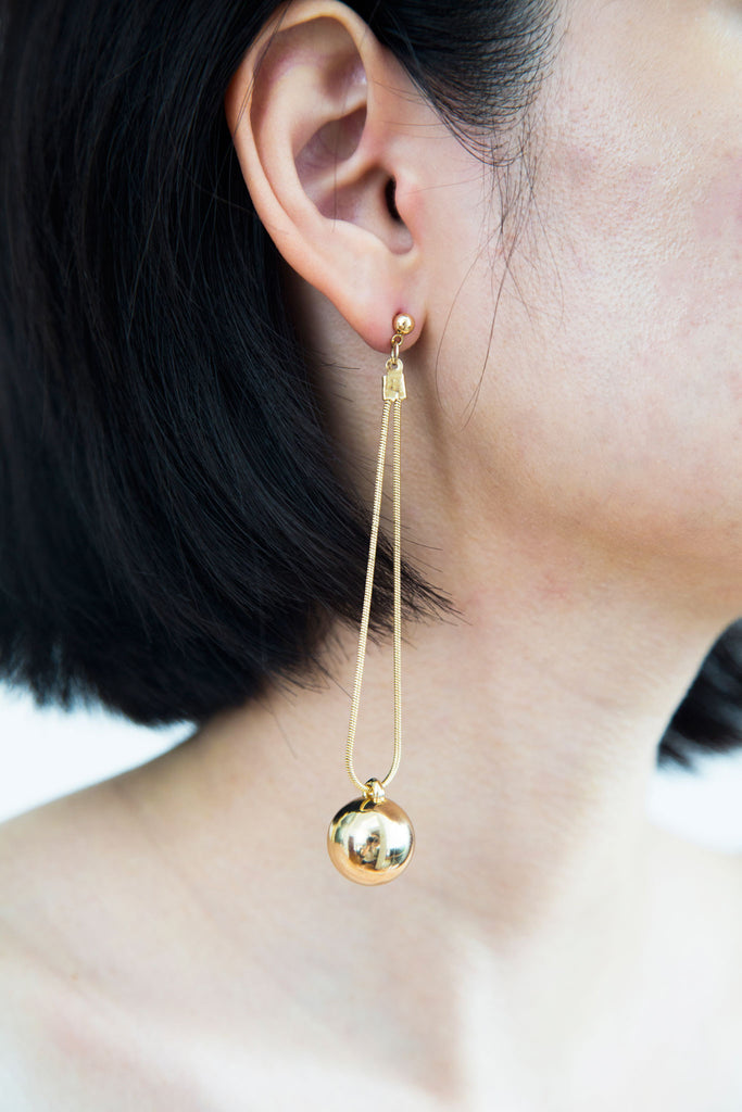 Suspended from an intricate gold chain, the gold ball charm gives of an aureate brilliance that sophisticates your outfit. Minimal and alluring, the Sophie earrings is a flawless addition to your next outfit.