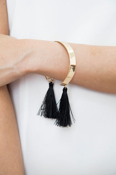 Affordable modern jewelry. A bold cuff with a brilliant flair. Two black tassels that sway its silky threads gracefully. The ideal addition to any classic and fun look.