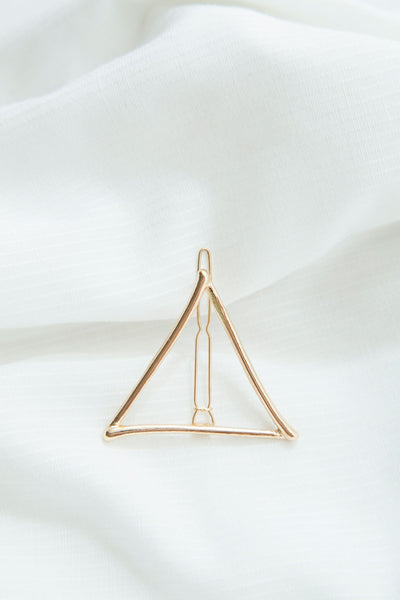 Modern triangle barrette in sleek gold tone metal. Complete with a secure clip and metal teeth to keep tresses in place.