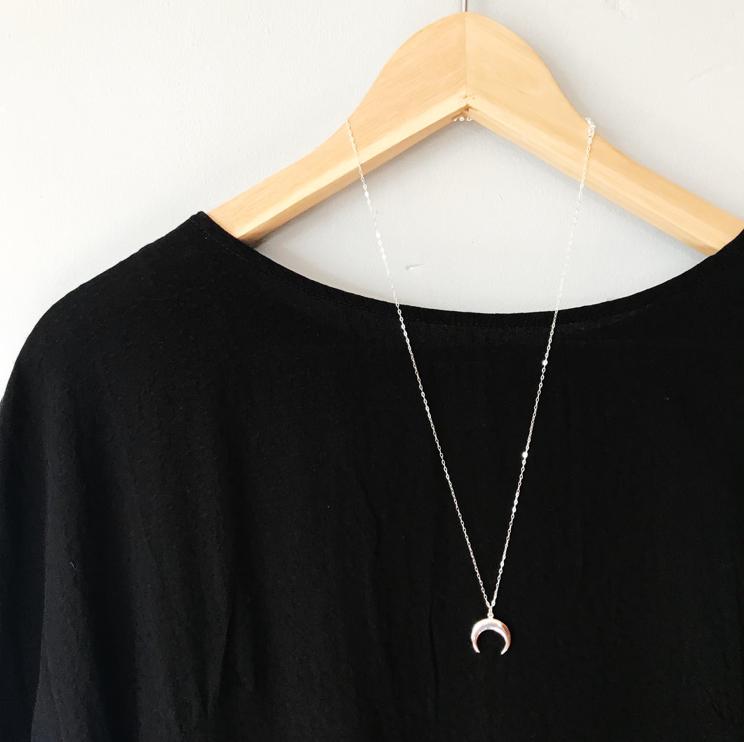 Grande crescent moon necklace shown on