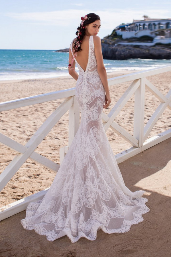 The Eris Wedding Dress by Bridal Designer Atelier Pronovias. The Eris gown is crafted in all-over Chantilly lace with delicate, floral motifs and intricate dotted details embroidered symmetrically from the deep, V-neck bodice to the edge of the soft, flowing train.