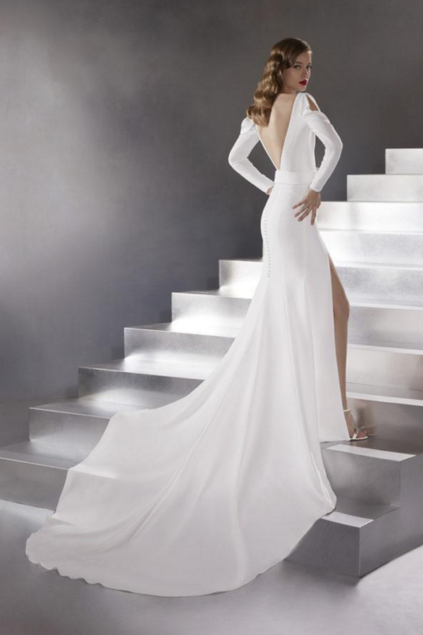 The Rocket Wedding Gown by Bridal Designer Atelier Pronovias. A crepe mermaid dress by Atelier Pronovias in all white with a high-slit skirt, a plunge neckline, a sparkling, buckled belt and long sleeves that open at the shoulders.