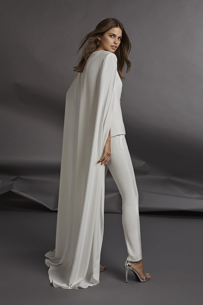 The Unconventional Wedding White Tuxedo by Bridal Designer Atelier Pronovias. From a tuxedo with an extra-long cape to a strapless jumpsuit. The versatility of this look allows it to go from a formal, elegant style for the wedding ceremony to a glamorous look, ideal for the post-wedding dance. (Off white)
