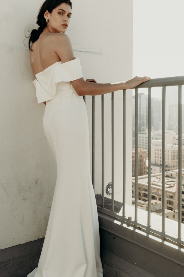 The Off Shoulder Bridal Bustier by Wedding Designer NEWHITE. Structural and elegant, the I.O. gown is essential for the modern bride with a twist. The deep inset adorned with our soft, pleated tulle adds allure while the arrangement of the off the shoulder sleeve creates a beautiful silhouette. (White)
