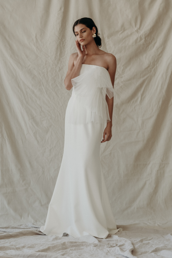 Wedding Dress by Bridal Designer NEWHITE. Exquisitely unique, the T.F. gown takes lead from runway looks. The curvature of the delicately pleated tulle sits perfectly upon a sleek and timeless silhouette. This style is perfectly uptown and couture. The pleated tulle part can be worn up or down. (White)