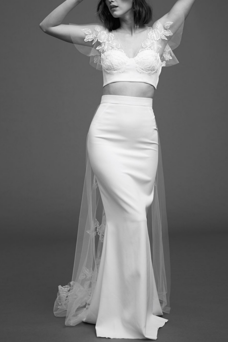 The Kim Top is designed by Rime Arodaky  pairs wonderfully with most bridal skirts or high-waisted trousers. Featuring sheer butterfly sleeves and back, this bustier crop top is a wedding look to be remembered. (White)