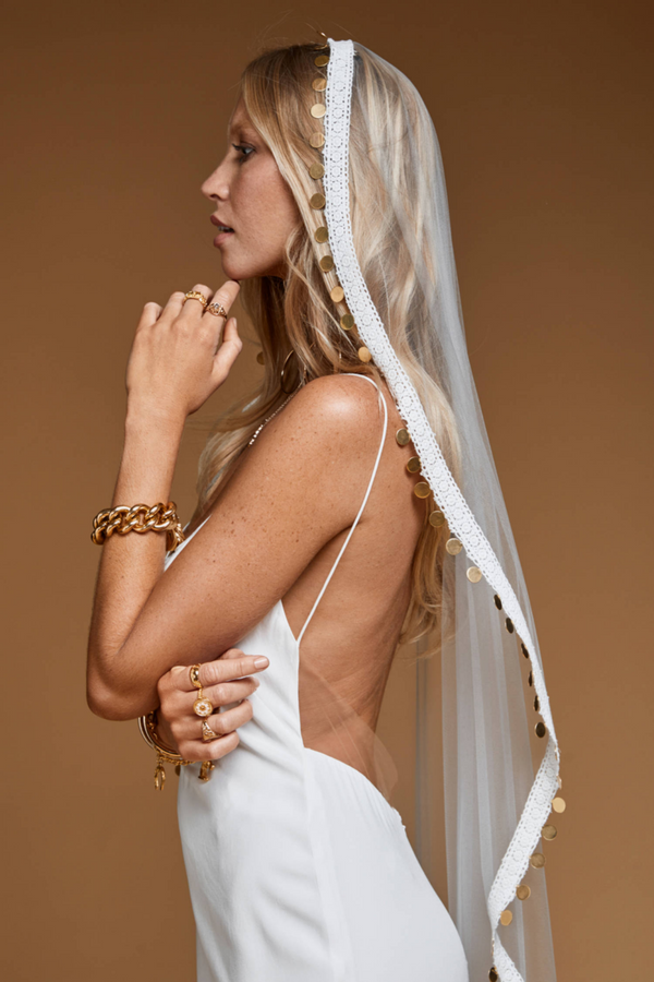 The Bridal Coin Veil by Wedding Designer Rue De Seine. The festival inspired Coin Veil is the perfect addition to any bohemian gown. The veil is hand embroidered using coins and crochet to create a romantic modern look. (Off White)