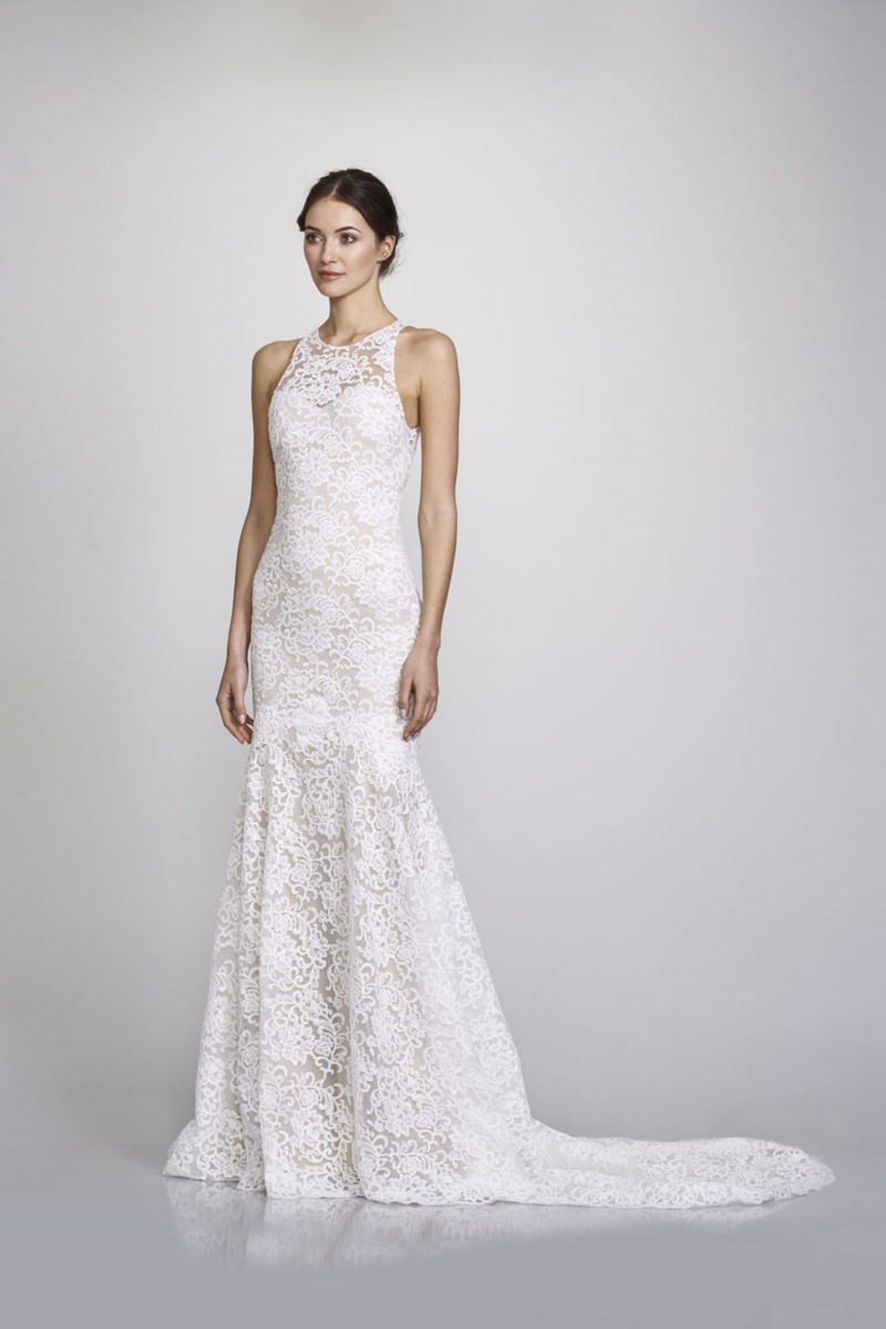 Sarah Wedding Gown by Bridal Designer Theia. Sarah is a romantic fit + flare gown with a timeless sheer high neck, soft cotton lace, & a flowing chapel length train. (Off white)
