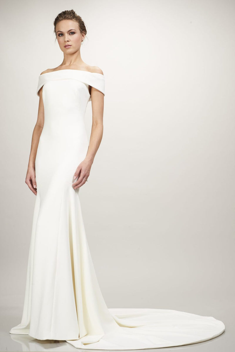 The Eve Wedding Dress by Bridal Designer Theia. The simplicity and elegance of the stretch crepe gives this gown a timeless appeal. The streamlined silhouette and off-the-shoulder sleeves, collarbone-baring-neckline makes this a grandiose style. (Ivory)