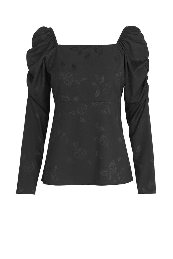 "A black feminine blouse with a squared neckline and puff sleeves in a cool rose weaved fabric. Made from 100% recycled polyester made from plastic waste. Cras only uses certified sustainable and natural fabrics, which reduces the footprint of our products immensely. The fabrics range from certified recycled polyester, the new ""green"" type of viscose Eco Vero, natural silk and organic cotton."