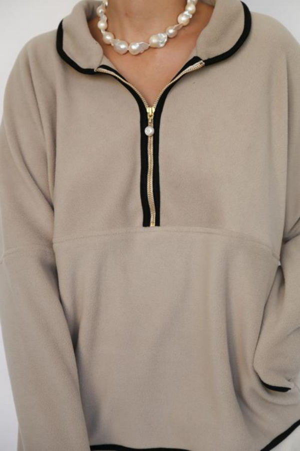 Loungewear elevated. Designed by Donni, this polar fleece 1/2 zip pullover features a stunning freshwater pearl zipper. These days, another comfortable sweater is always welcome to our collection of lounge or WFH options.