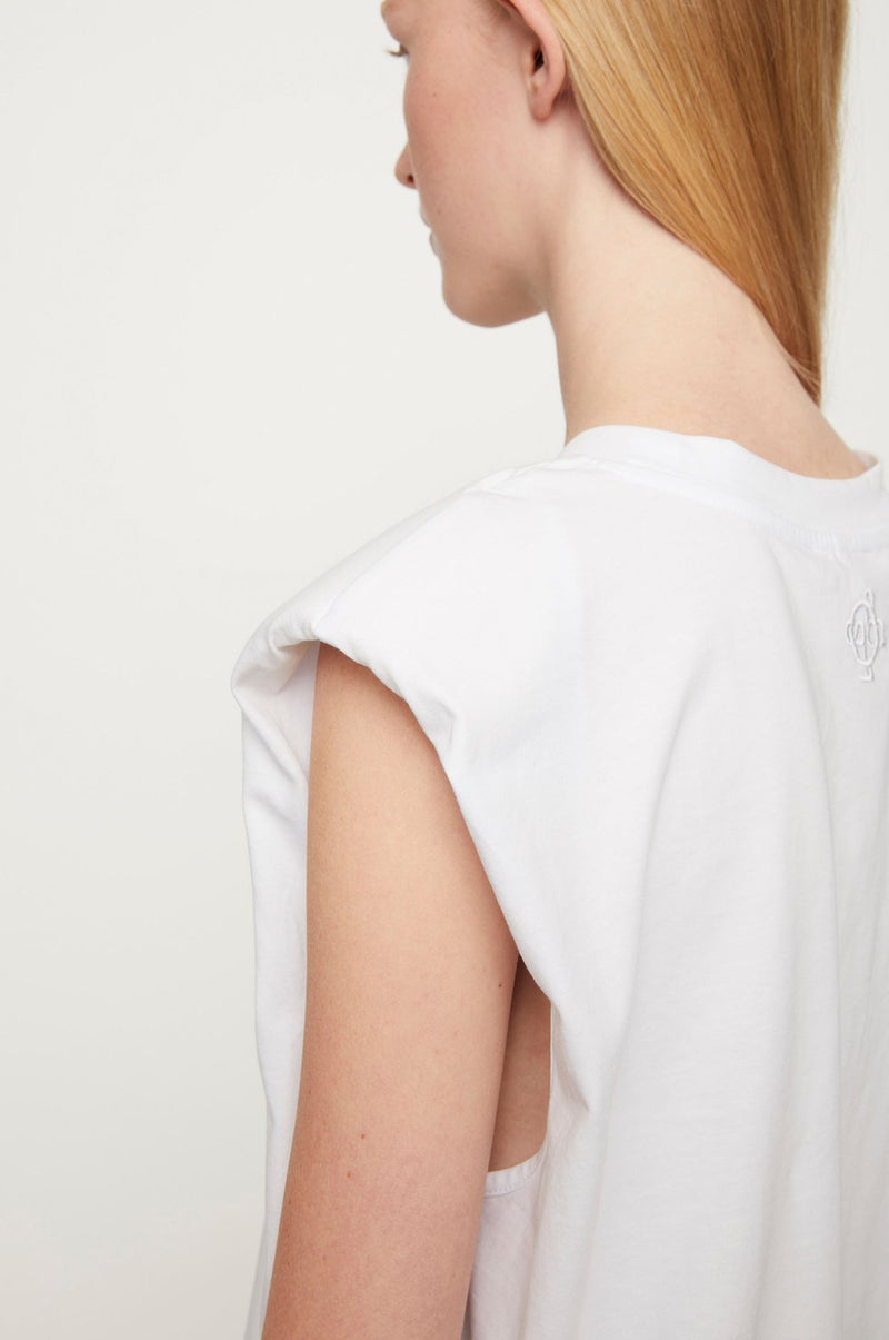 The Beijing White Top is a cool masculine top made from 100% organic cotton. This basic classic tee with a twist is sleeveless and has accentuating shoulder pads and an embroidered tone-in-tone JUST emblem on the back. Designed by Just Female and perfect to pair with your favourite pair of jeans for an elevated casual look.