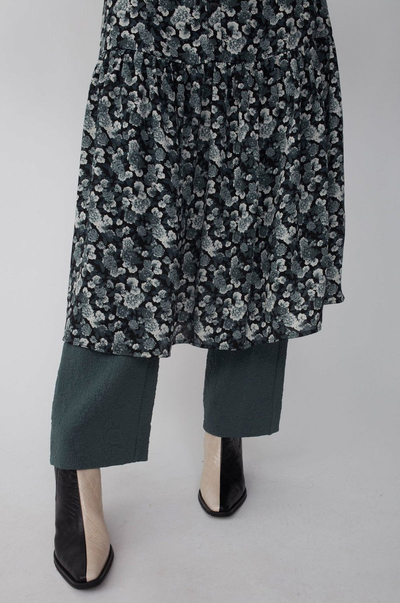 The Effie Maxi Dress designed by Just Female, is made from recycled polyester in an all-over flower print. The dress is loose fitted and has extra width in the bottom. The long sleeves are voluminous with cuff. It as a round mandarin collar and button-down closing.