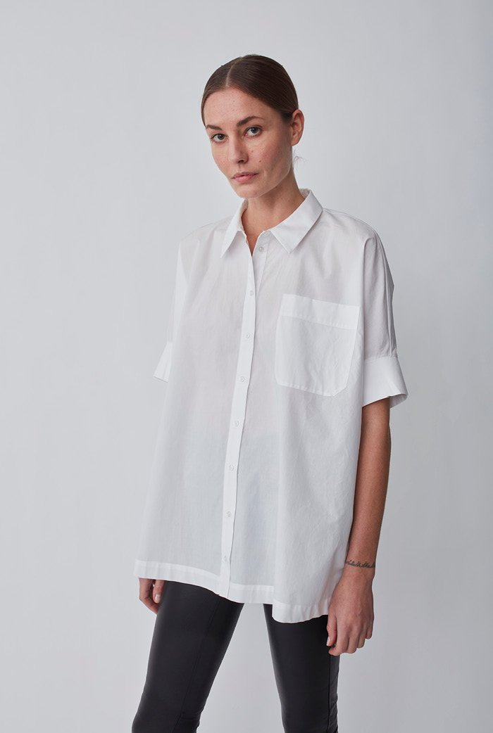 Who doesn't need another white button-down added to their wardrobe? This classic short-sleeved shirt is made from crisp and organic cotton. The shirt has a classic collar with visible button fastening, breast pockets, slits on the sides and the short sleeves are finished with a broad band. The fit is oversize. ESSENTIALS is an exclusive line of wardrobe must-haves that never go out of style. Perfect for every day wear.