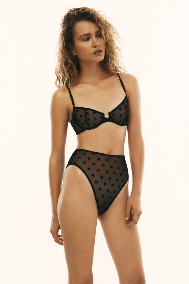 Designed by Le Petit Trou, the Abelle underwire bra is made of black, stretchy material in bows pattern covered with glitter powder. The front embellished with bow- like folding. Fastened with hooks at the back and the straps are easily adjustable.