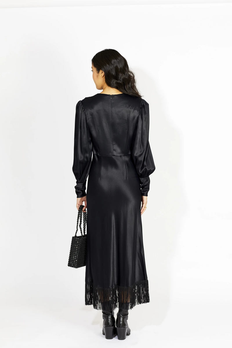The Challans Black Dress designed by Le Petit Trou features a satin feel and is embellished with fringes and voluminous puffed sleeves. The perfect dress for yor next date night or evening out. Made in Poland.