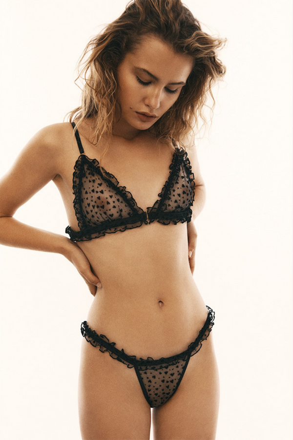 Designed by Le Petit Trou the Dorine triangle bra is made of see-through material in flocked hearts. Decorative tight frilling at the cups and underbust. The bra has an opening at the front for additional comfort and the straps are easily adjustable.