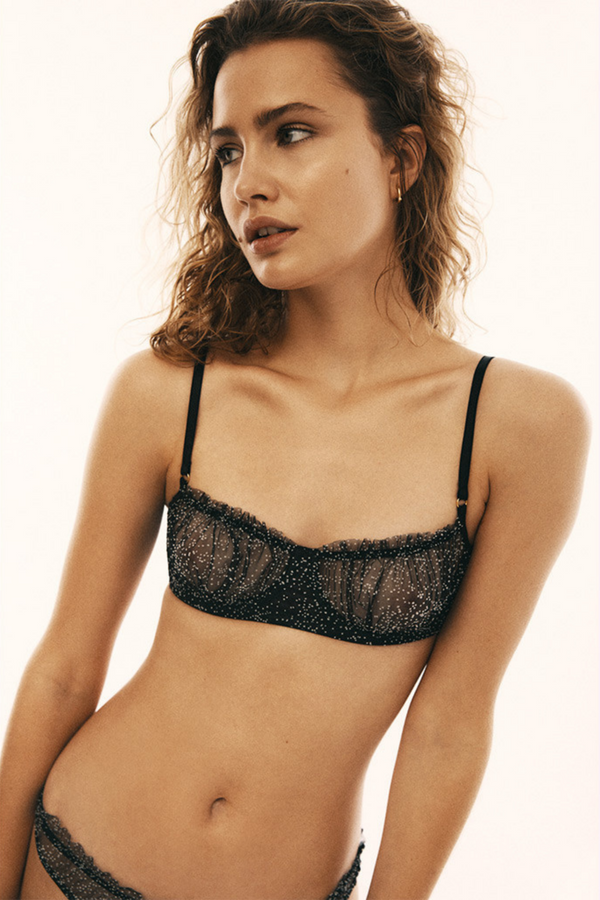 Underwire soft bra made of elastic and smooth black material in small white dots. Embellished with delicate ruffling at the top and draping at the cups. Fastened with hooks at the back and the straps are easily adjustable. And don't worry, the ruffles won't be visible from underneath the t-shirt.
