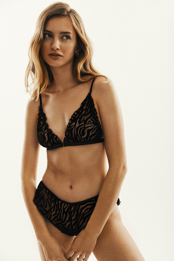 The Naomi soft bra made of black material in flocked, zebra pattern. The delicate ruffles at sides are a well known Le Petit Trou detail. The bra has an opening at the front for additional comfort and the straps are easily adjustable.
