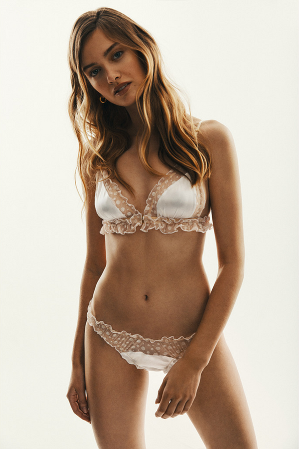 The Oriane Bra is a soft bralette made of stretchy nude see-through material in white, shimmering dots and the filling of 100% silk. The delicate ruffles at sides and bottom are a well known Le Petit Trou detail. Bra has an opening at the front for additional comfort and the straps are easily adjustable. The bra is a unique take on a bridal lingerie, more trendy and fun than traditional.